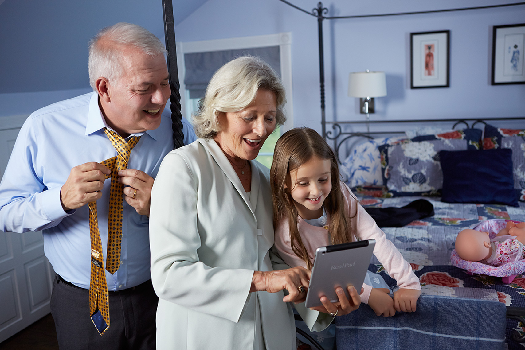 grandparents and granddaughter in bedroom with tablet