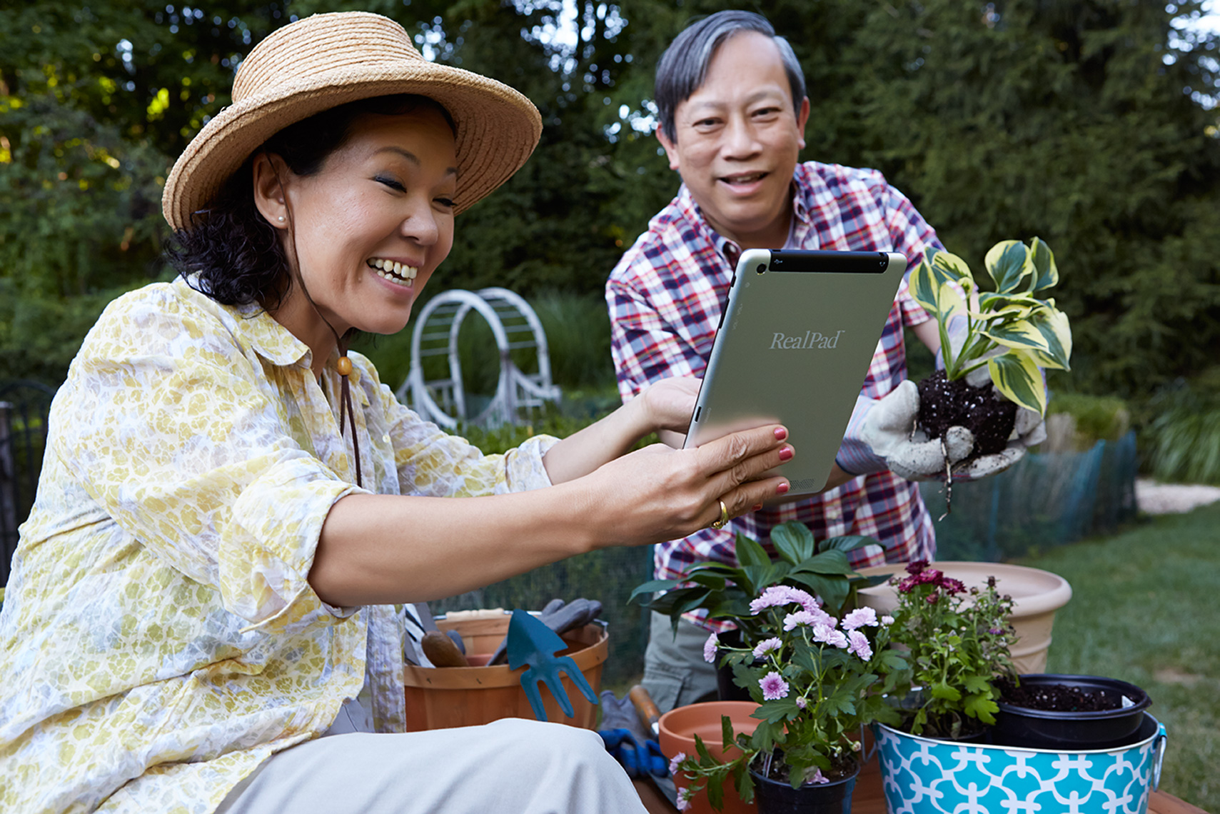 asian couple in garden with tablet