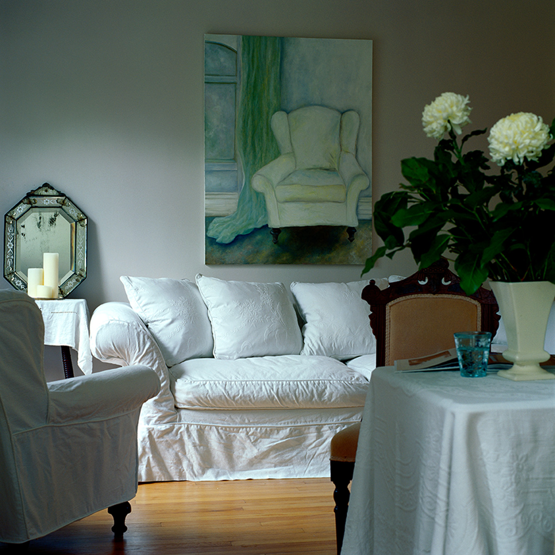 living room with white shabby chic sofa and primitive painting