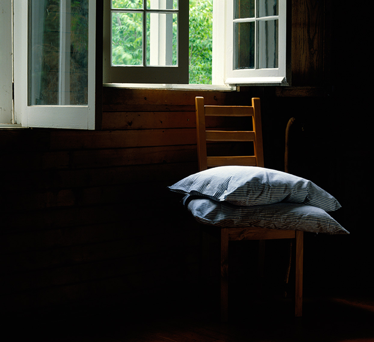 pillows on wooden  chair by window