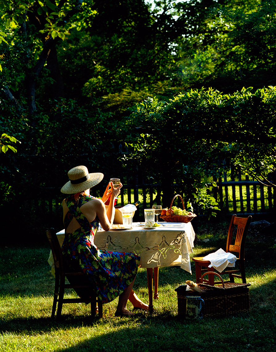 woman in yard with table wine and food