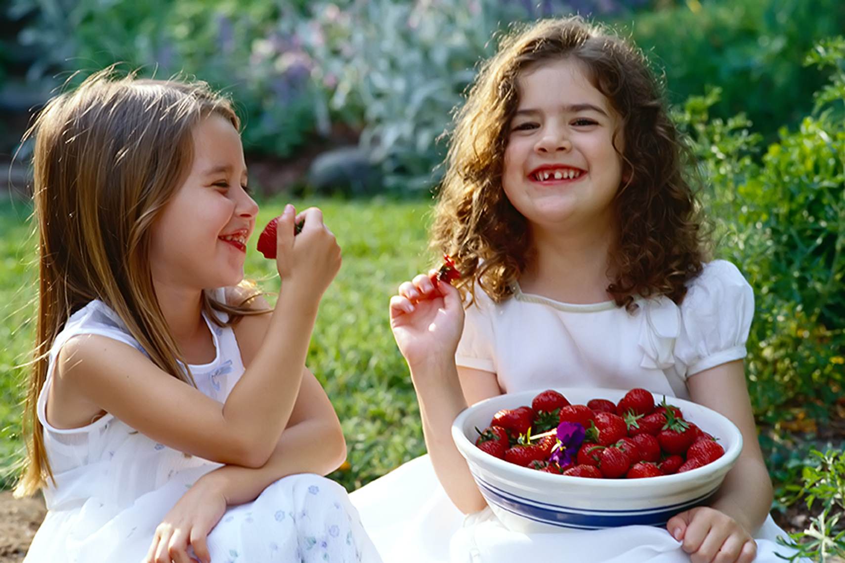 little girls eating strawberries
