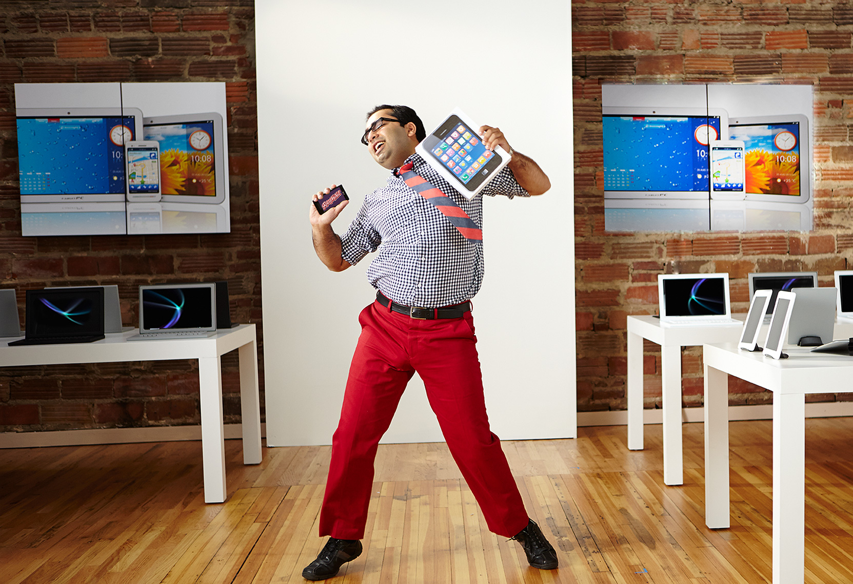 man dancing in a computer store with tablet
