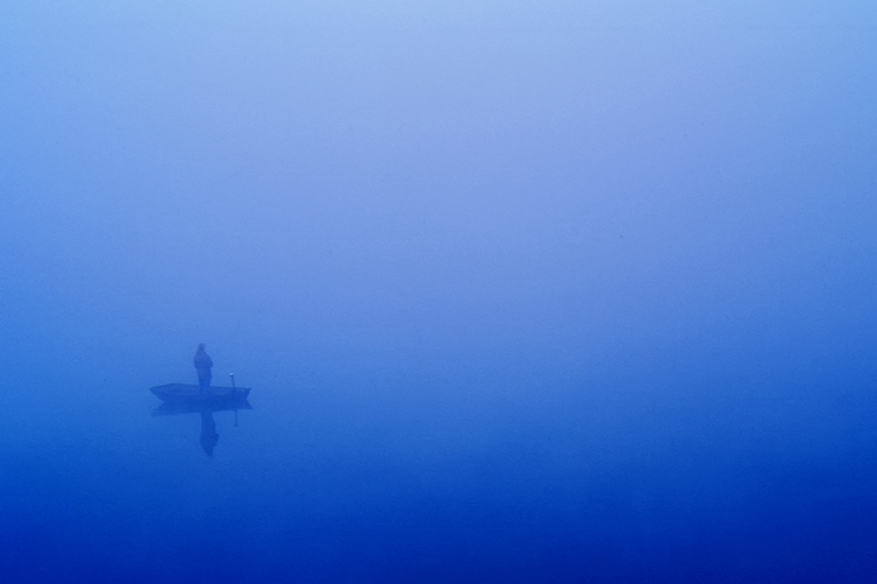man fishing in boat in blue fog