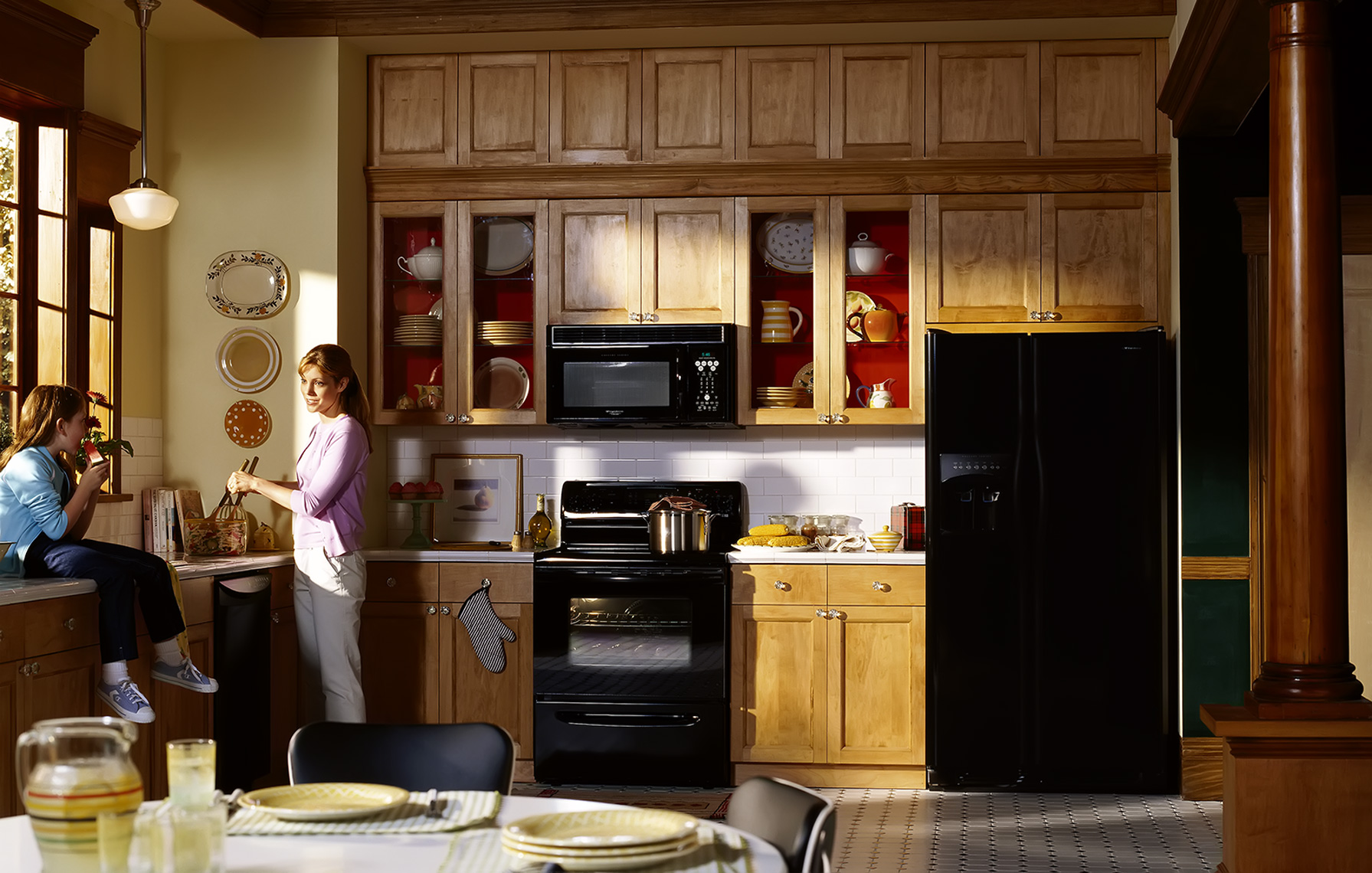 mother and daughter in kitchen with black appliances