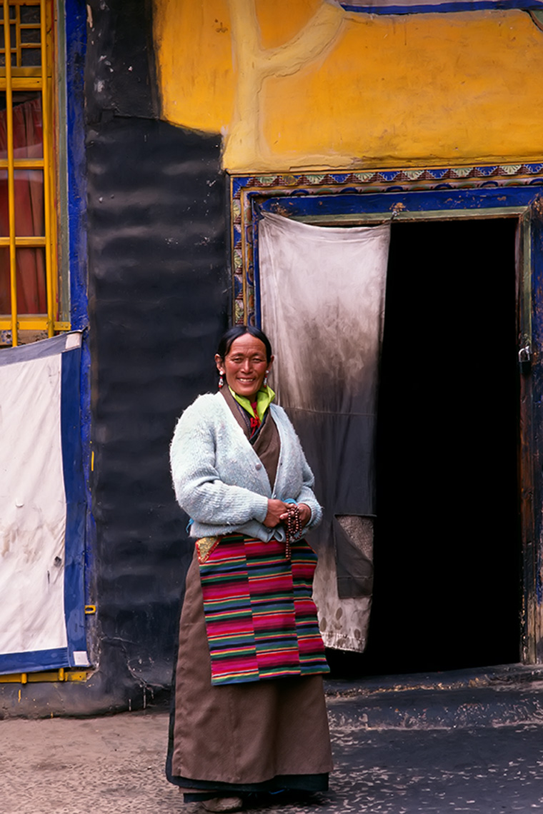 lhasa tibet woman yellow wall blue trim fabric