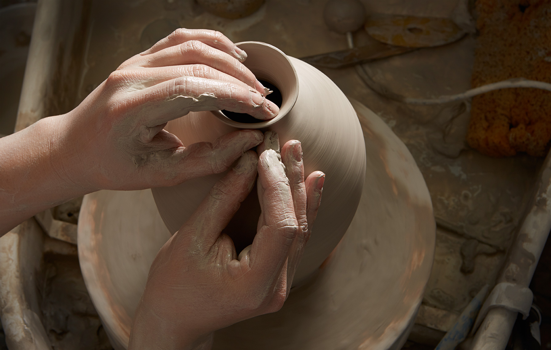 potters hands throwing clay pot