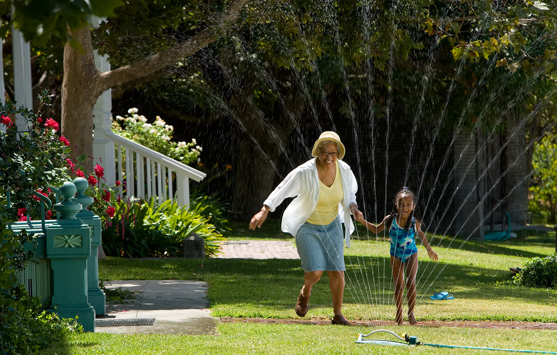 grandmother jumping through sprinkler