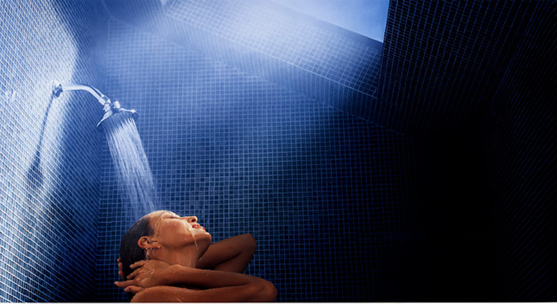 woman in shower with skylight and blue tile